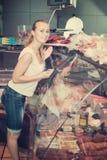 Femme positive regardant des produits carnés Photographie stock