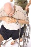 Femme poussant l'homme dans le fauteuil roulant Images libres de droits