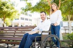 Femme poussant l'homme dans le fauteuil roulant photo stock