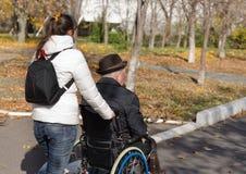 Femme poussant un homme plus âgé dans un fauteuil roulant Photos stock