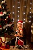 Femme près de l'arbre de Noël effectuant le cadeau Photographie stock libre de droits