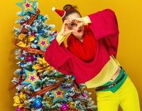 Femme près de l'arbre de Noël montrant les mains en forme de coeur Photographie stock