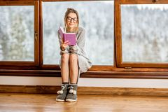 Femme près de la fenêtre pendant l'hiver image stock