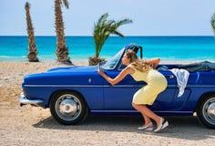 Femme près de rétro voiture de cabriolet Photo stock