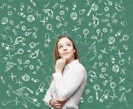 Femme près de tableau noir vert avec des icônes d'éducation Image libre de droits
