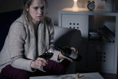 Femme préoccupée versant le vin rouge images stock