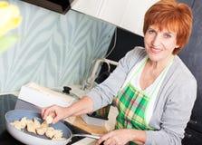 Femme préparant des pâtes avec du fromage Photo stock