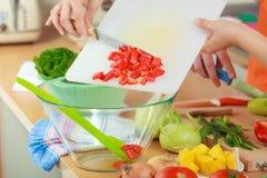 Femme préparant la salade de légumes coupant en tranches le poivron rouge Image stock