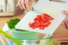 Femme préparant la salade de légumes coupant en tranches le poivron rouge Photos libres de droits