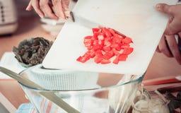 Femme préparant la salade de légumes coupant en tranches le poivron rouge Photo libre de droits