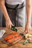 Femme préparant le filet saumoné avec la marinade Photo libre de droits