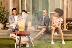 Femme préparant le gril de barbecue sur le patio tandis que ses amis s'asseyant au porche Photographie stock