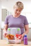Femme préparant le panier-repas malsain dans la cuisine images libres de droits