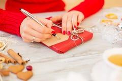 Femme préparant le présent et écrivant sur la carte Photos stock