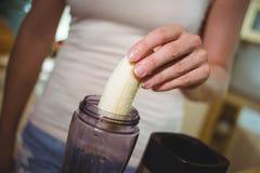 Femme préparant le smoothie de banane Photos stock