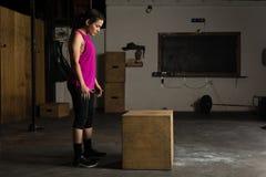 Femme prête à sauter sur une boîte photos stock