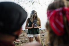 Femme prenant à amis la photo par le rétro appareil-photo sur le voyage par la route Photo libre de droits