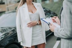 Femme prenant avec le travailleur près de la voiture dehors images stock