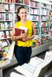 Femme prenant des livres de littérature dans le magasin Photo stock