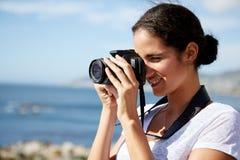 Femme prenant des photos de l'océan photographie stock libre de droits
