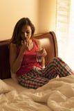 Femme prenant des pilules dans le lit Photos libres de droits