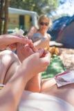 Femme prenant l'épine d'oursin hors de ses amis uniques utilisant l'aiguille médicale Image stock