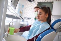 Femme prenant l'eau tout en se reposant dans la chaise dentaire photos stock