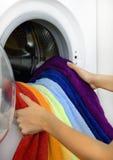 Femme prenant la blanchisserie de couleur de la machine à laver photo stock