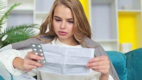 Femme prenant la médecine Beau jeune habillage transparent se tenant femelle avec des pilules disponibles et lisantes des instruc clips vidéos