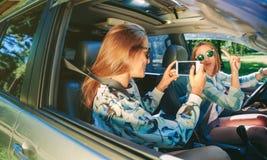 Femme prenant la photo à son ami à l'intérieur de voiture Image stock