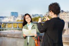 Femme prenant la photo de son ami près de la Seine Images libres de droits
