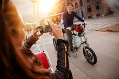 Femme prenant la photo des amis sur le tricycle Photos libres de droits