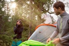 Femme prenant la photo du camping accrochant proche de tente de l'homme avec la fusée du soleil Groupe de voyage d'aventure d'été Photo stock