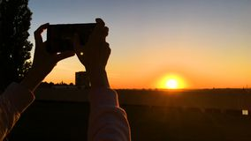 Femme prenant la photo du coucher du soleil avec le smartphone dans la ville clips vidéos