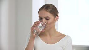 Femme prenant la pilule, eau potable de verre dans l'intérieur blanc clips vidéos