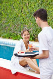 Femme prenant le cocktail du serveur à la piscine d'hôtel Photographie stock libre de droits
