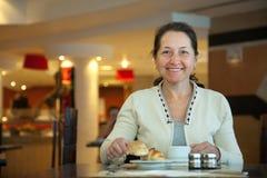 Femme prenant le petit déjeuner Photo stock