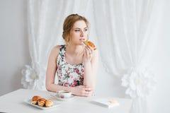 Femme prenant le petit déjeuner avec le thé et les croissants frais faits maison Photo stock