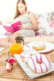 Femme prenant le petit déjeuner dans le lit tout en lisant un livre Images libres de droits