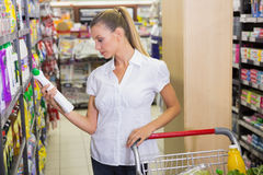 femme prenant le produit d'entretien dans l'étagère du bas-côté Images stock