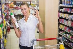 femme prenant le produit d'entretien dans l'étagère du bas-côté Photos libres de droits