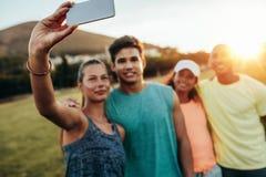 Femme prenant le selfie avec des amis au parc Photos stock