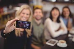 Femme prenant le selfie avec des amis de téléphone portable au café Images libres de droits