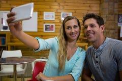 Femme prenant le selfie avec l'ami par le téléphone portable en café Photo libre de droits