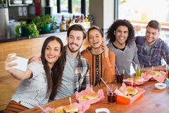 Femme prenant le selfie avec les amis gais dans le restaurant Images libres de droits