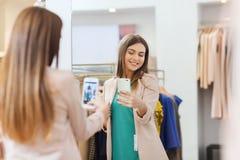 Femme prenant le selfie de miroir par le smartphone au magasin Photo libre de droits