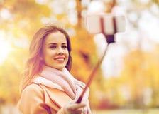 Femme prenant le selfie par le smartphone en parc d'automne Photos libres de droits