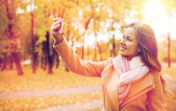 Femme prenant le selfie par le smartphone en parc d'automne Photographie stock