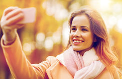 Femme prenant le selfie par le smartphone en parc d'automne Photos stock