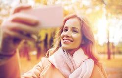 Femme prenant le selfie par le smartphone en parc d'automne Images stock